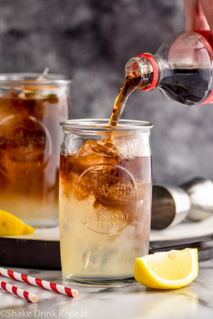 Man pouring ingredients into a glass of long island iced tea with ice, lemon and cola