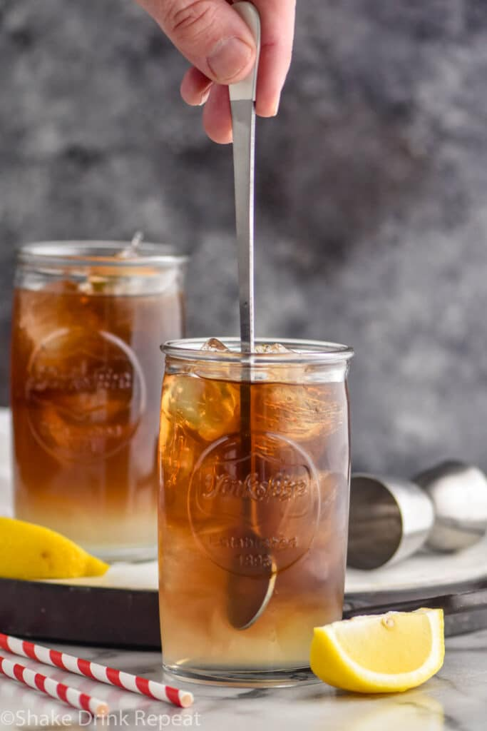 man stirring a glass of long island iced tea with ice and lemons
