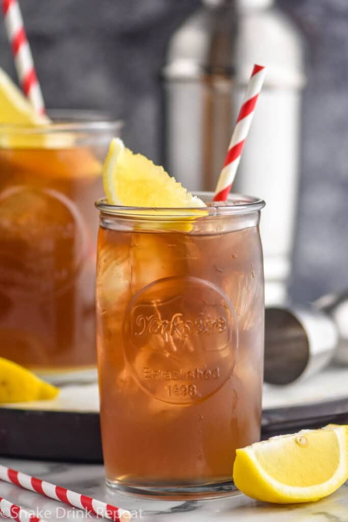 two glasses of long island iced tea with ice, straws, and lemons