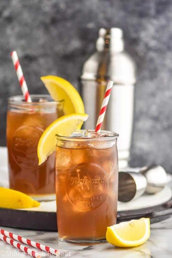 two glasses of long island iced tea with ice, straws, and lemon garnish