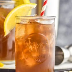 two glasses of long island iced tea with ice, a straw and lemon garnish