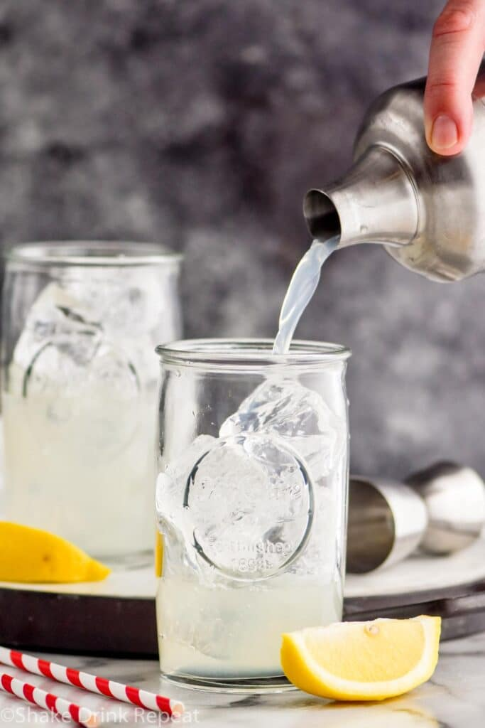 making two glasses of long island iced tea by pouring ingredients from shaker over ice with lemon garnish