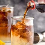pouring cola into a glass of long island iced tea with ice and lemon