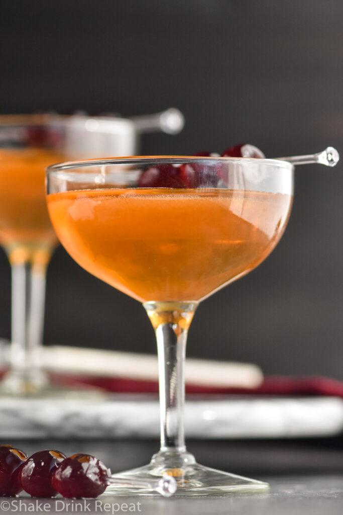 glass of Manhattan cocktail with cherries to garnish