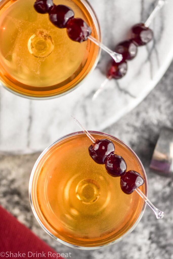 two glasses of Manhattan cocktails with cherries to garnish