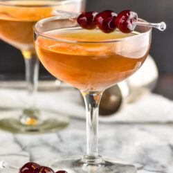 two glasses of Manhattan cocktails with cherry garnish