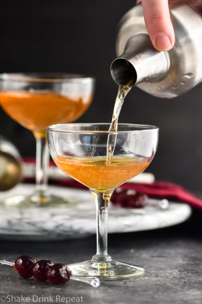 Making a Manhattan cocktail and pouring into a glass with cherry garnish