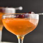 glass of Manhattan with cherry garnish