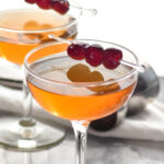 two glasses of Manhattan with cherry garnish