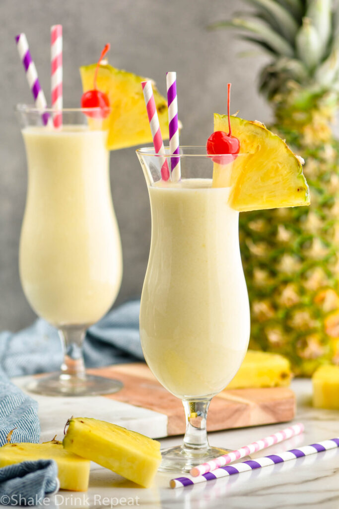 two glasses pina colada with straws, pineapple wedge, and cherry