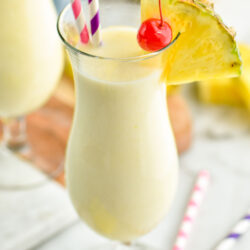 glass of pina colada with straws, pineapple wedge, and cherry