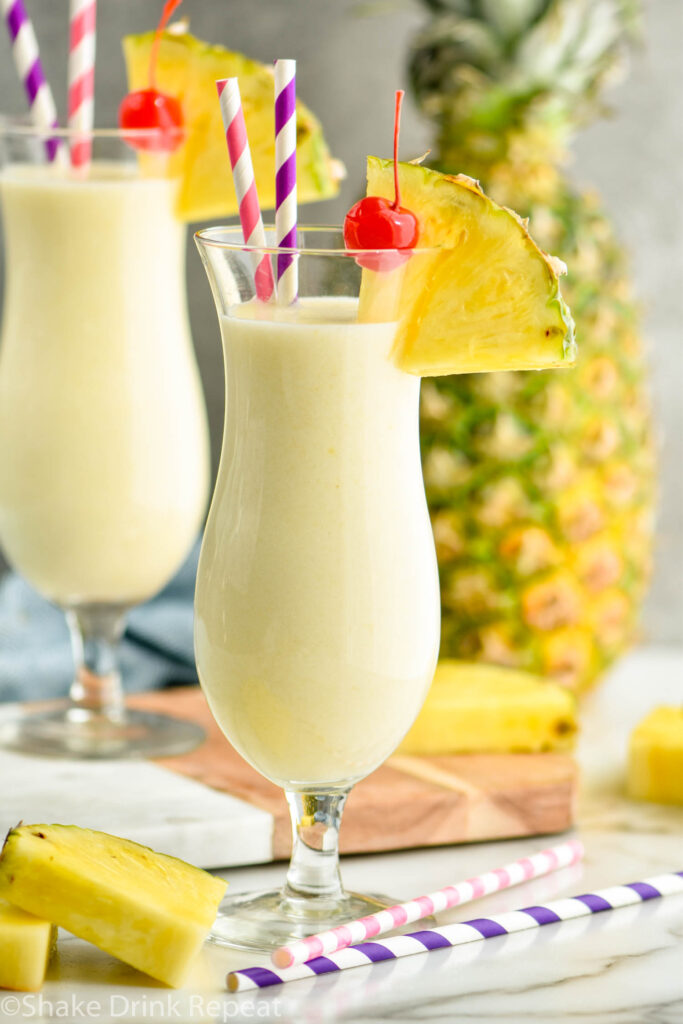 two glasses of pina colada with straws, pineapple wedge, and cherry