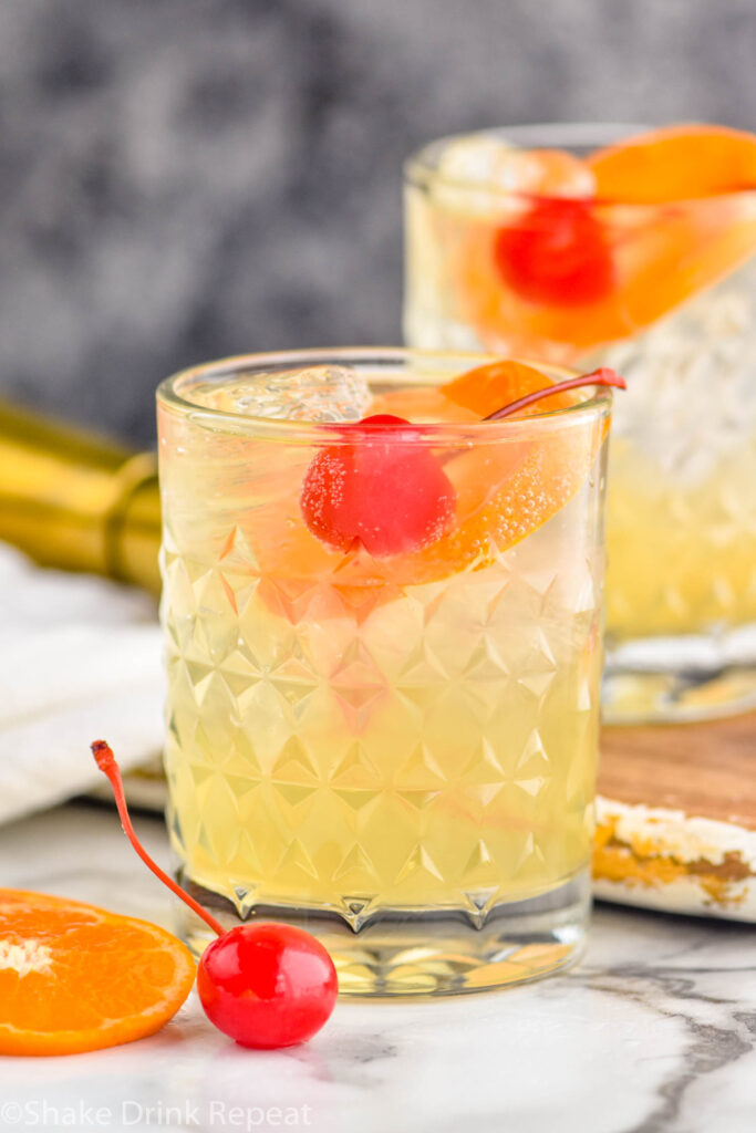 two glasses of Amaretto Sour with ice, orange slices, and cherry garnish