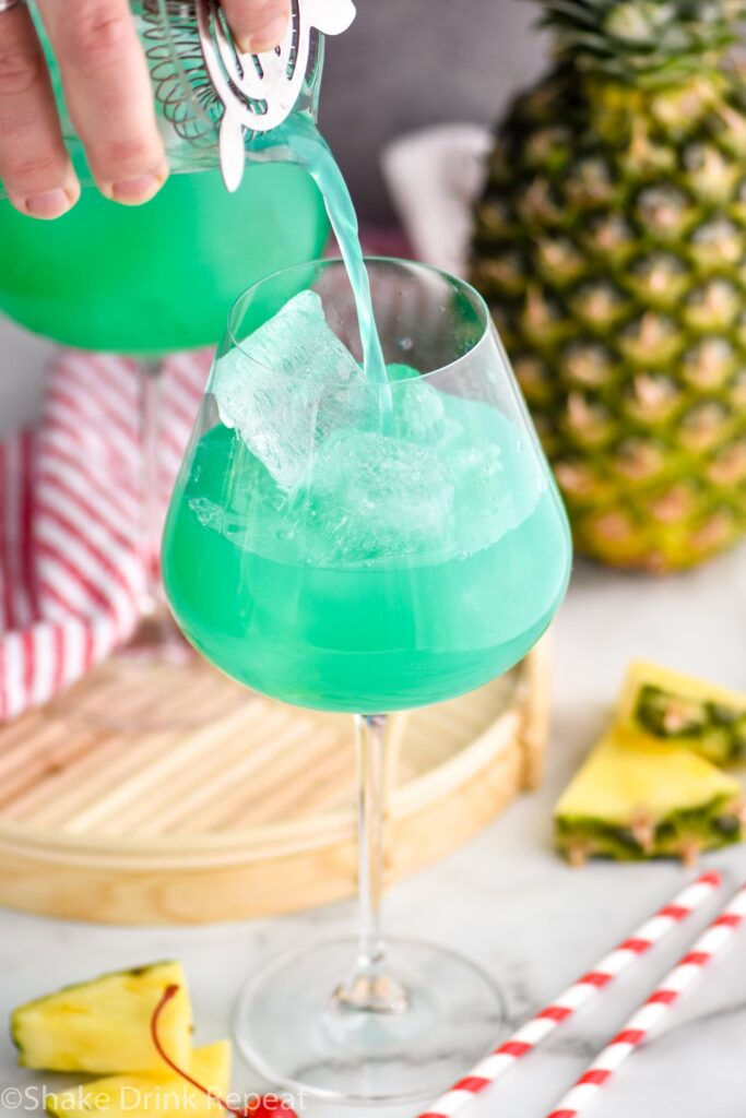 pouring a blue hawaii into a cocktail glass with ice, pineapple and cherry garnish