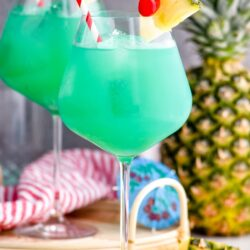 two glasses of blue hawaii with ice, straws, pineapple, and a cherry