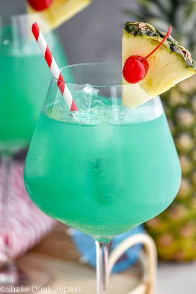 glass of blue hawaii with ice, a straw, pineapple, and a cherry