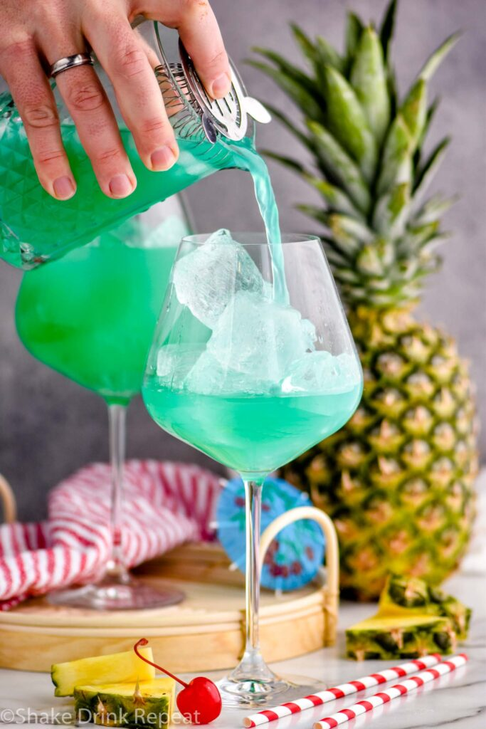 pouring a blue hawaii into a cocktail glass with ice surrounded by pineapple and a cherry.