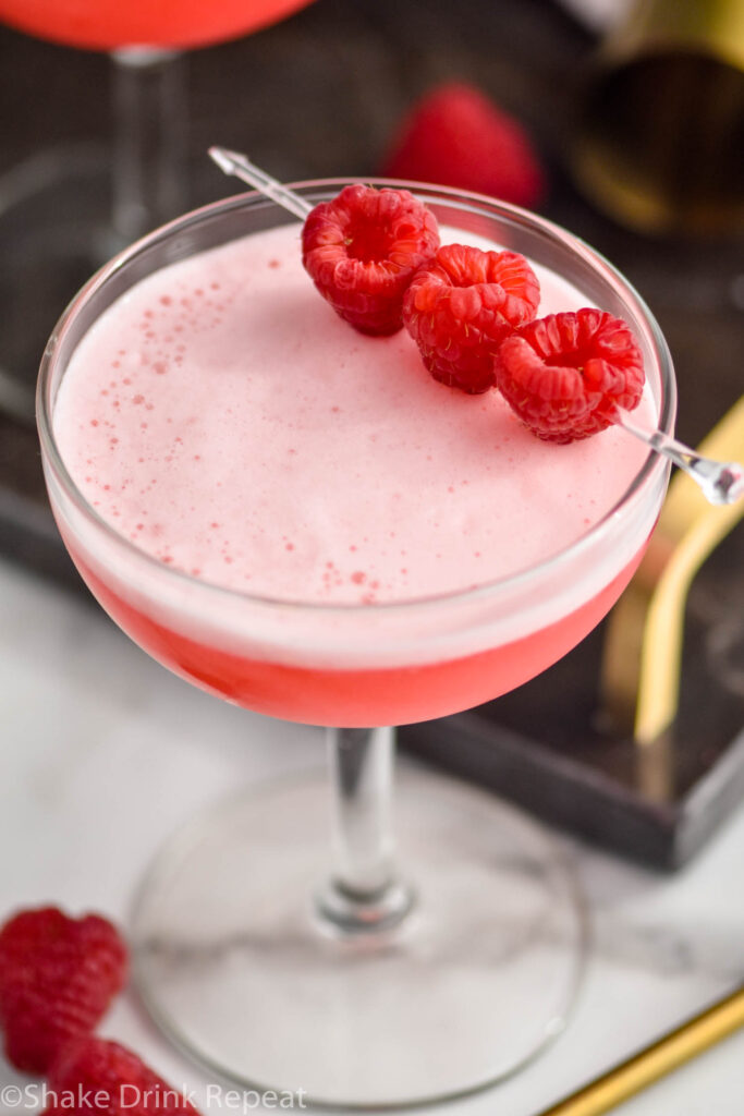 glass of clover club cocktail with raspberry garnish