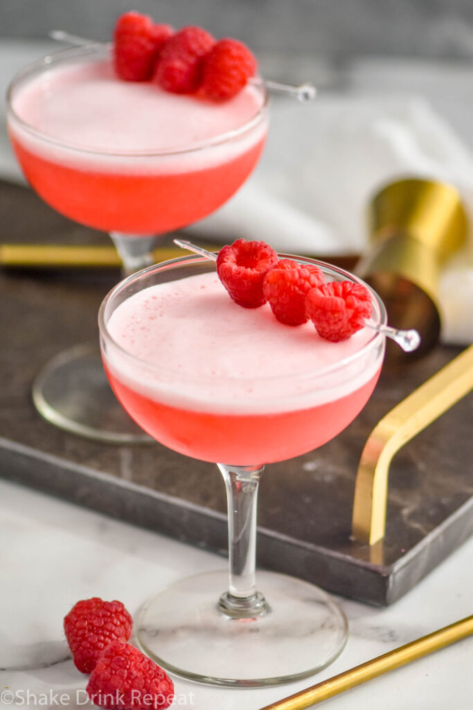 two glasses of clover club cocktail with raspberry garnish