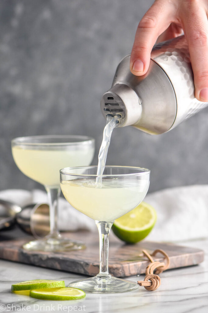 man pouring daiquiri from a shaker into a chilled cocktail glass surrounded by limes
