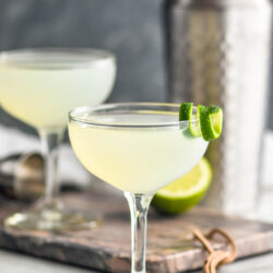 two cocktail glasses of daiquiri with lime twist