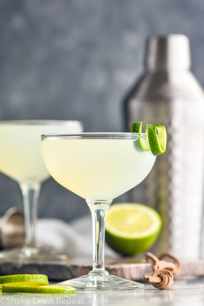 two cocktail glasses of daiquiri with lime twist and shaker in the background