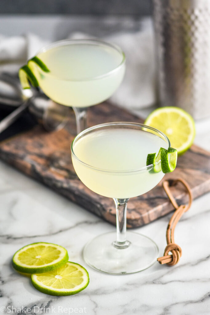 two glasses of daiquiri surrounded by lime slices