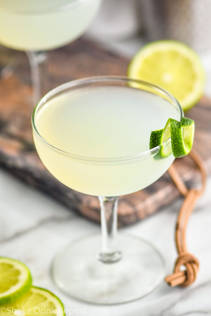 glass of daiquiri cocktail with lime twist