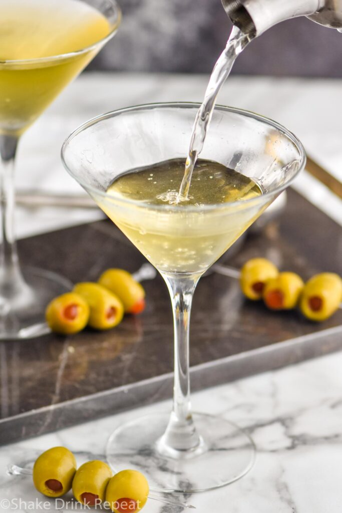 making a dirty martini in a glass with green olives