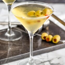 two glasses of dirty martini with green olives