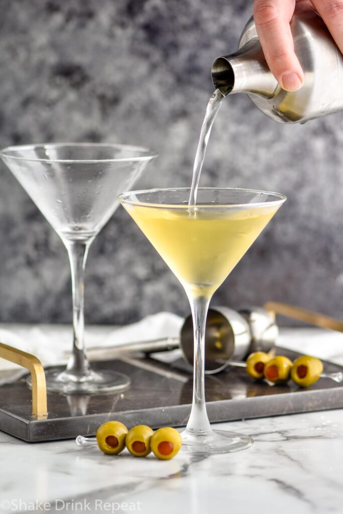 pouring a dirty martini into a martini glass with green olives