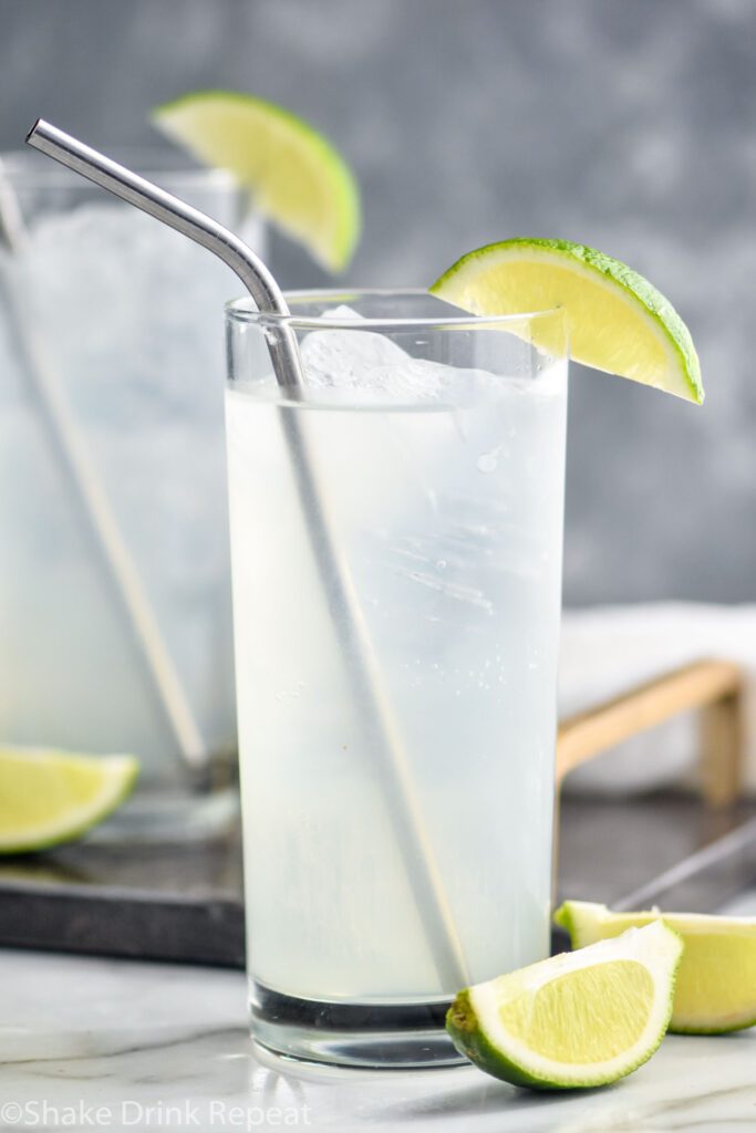 two glasses of gin rickey with ice, straws, and lime wedge garnish