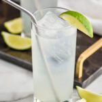 glass of gin rickey with ice and straw surrounded by lime wedges