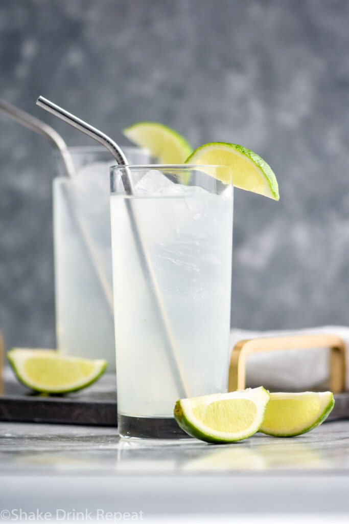 two glasses of gin rickey with ice, straws, and lime wedges