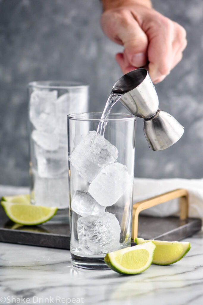 man pouring jigger of gin into a glass of ice to make a Gin Rickey surrounded by lime wedges