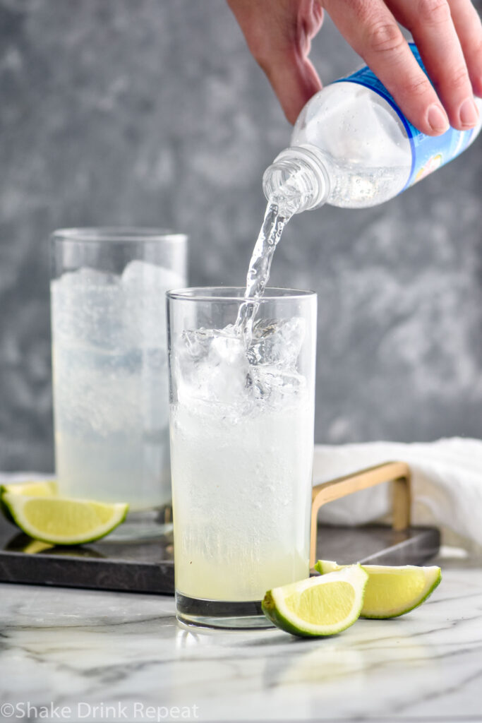 man pouring club soda water into a glass of Gin Rickey, ice, and lime wedges.