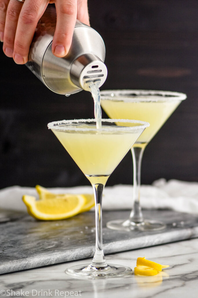 man's hand pouring lemon drop martini into a martini glass with sugared rim and lemon twist garnish