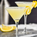 two glasses of lemon drop martini with sugared rim and lemon twist