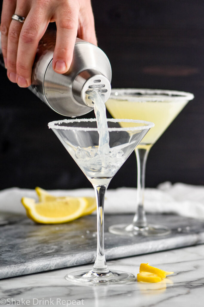 man pouring a lemon drop martini into a glass rimmed with sugar surrounded by lemon slices