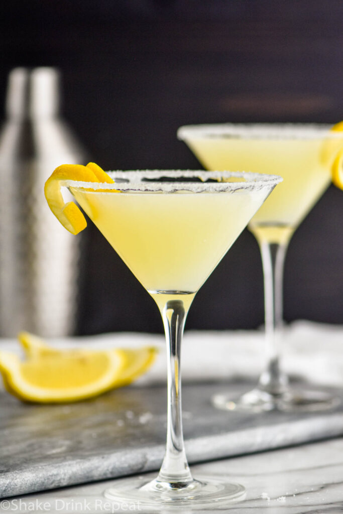 two glasses of lemon drop martini with sugared rims and a lemon twist