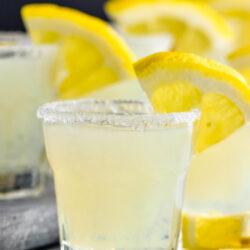 glasses of lemon drop shot with sugared rim and lemon wedge