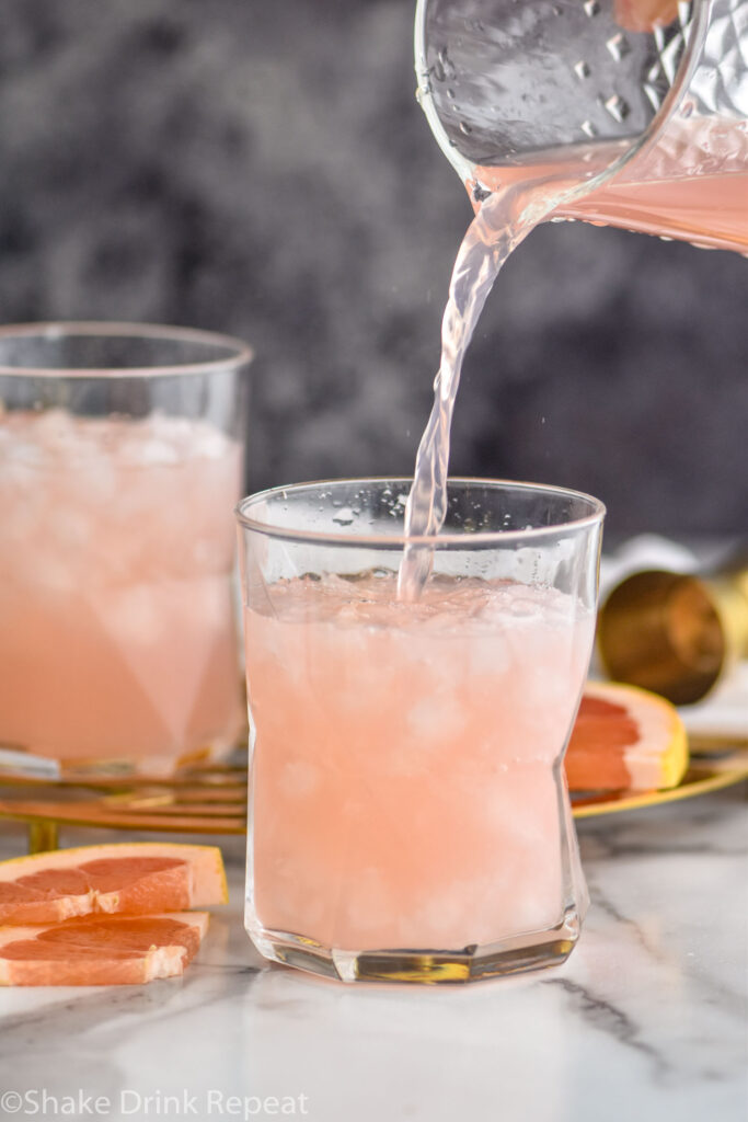 two glasses of paloma cocktail poured from a pitcher with crushed ice and grapefruit