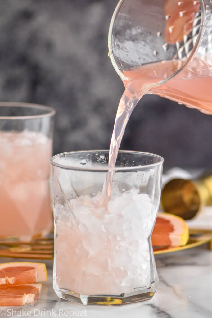 making a glass of Paloma cocktail with crushed ice and grapefruit