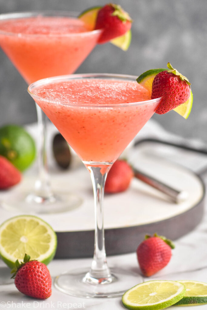 two glasses of strawberry daiquiri with fresh strawberries and limes