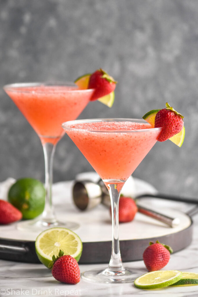 two glasses of strawberry daiquiri with fresh limes and strawberry garnish