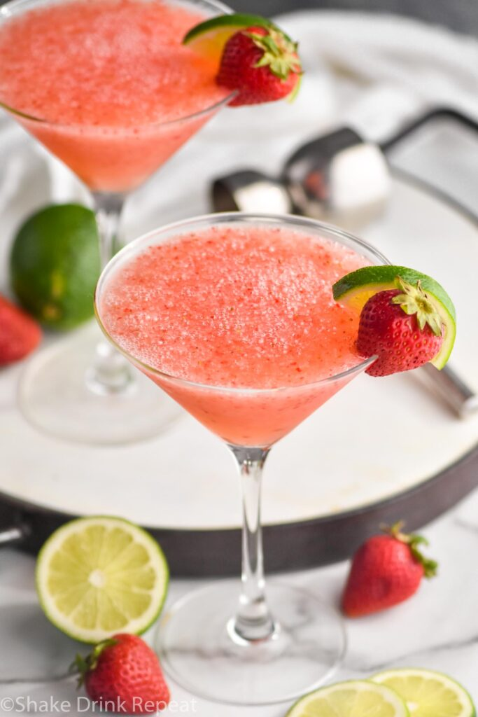 two glasses of strawberry daiquiri with fresh limes and strawberries