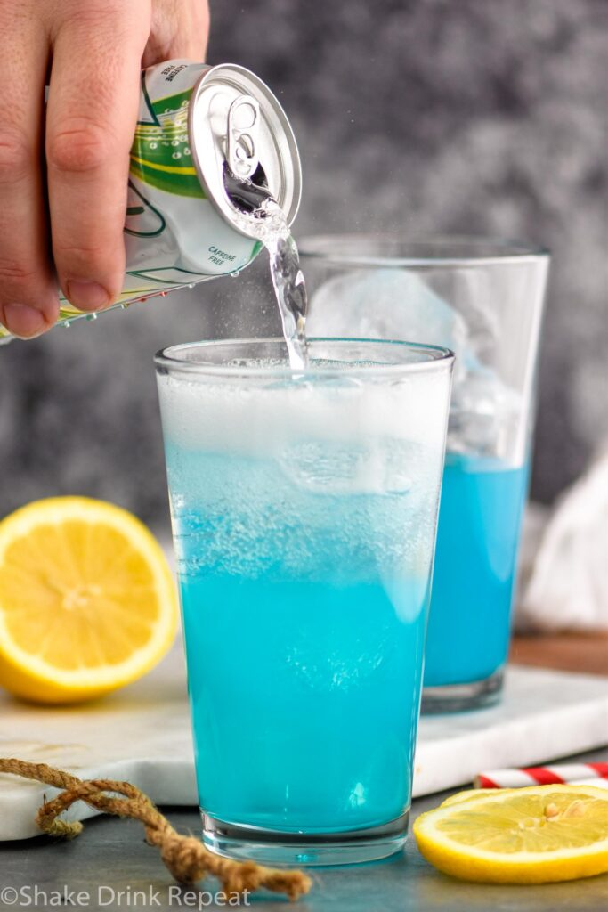 man pouring 7up into a glass of walk me down cocktail with lemons and ice