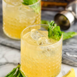 two glasses of whiskey smash with ice, mint and lemon
