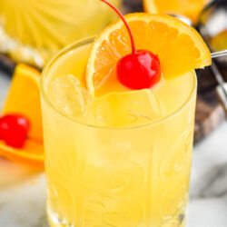 glass of Amaretto Stone Sour with ice, orange slice, and cherry garnish