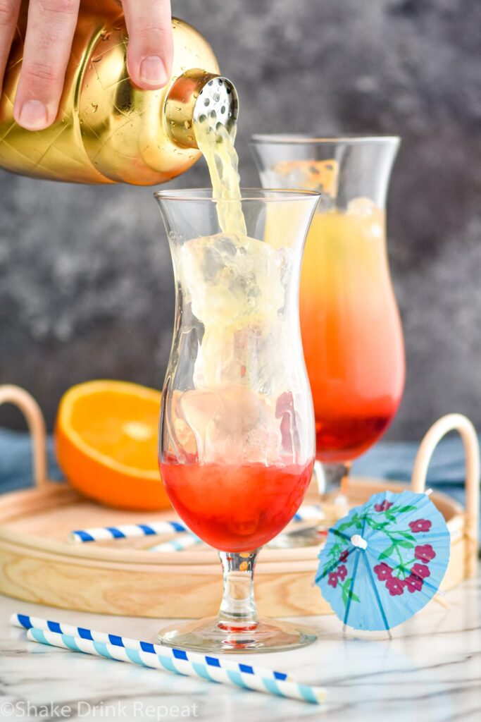 man pouring bahama mama ingredients from a shaker into a glass filled with ice surrounded by straws and a cocktail umbrella